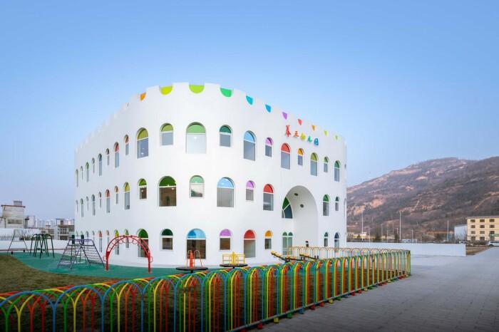 Детский садик выглядит очень нарядно с белыми стенами и цветными стеклами. /Фото: images.adsttc.com