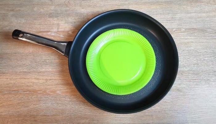 Бумажные тарелки помогут сберечь покрытие при складывании сковородок штабелем. /Фото: youtube.com