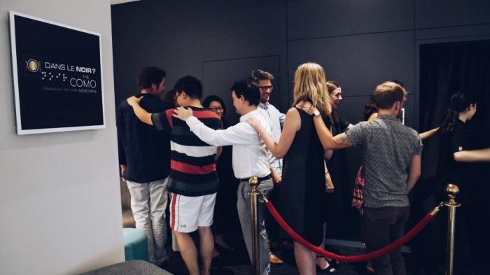 Посетители направляются в зал ресторана Dans le Noir?, держась друг за друга. /Фото: goodfood.com.au