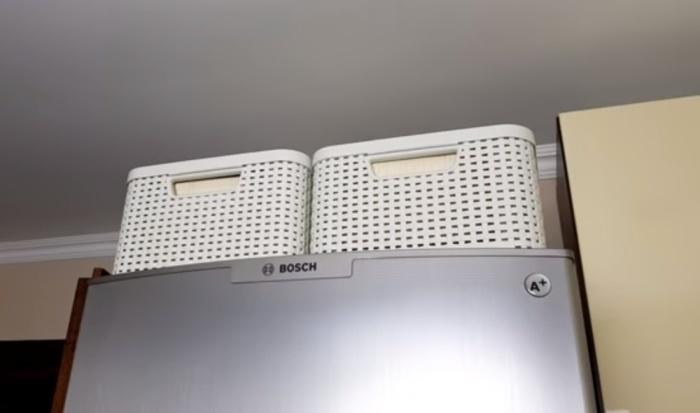 Место на холодильнике можно использовать для хранения, поставив туда объемные коробки с кухонными мелочами.