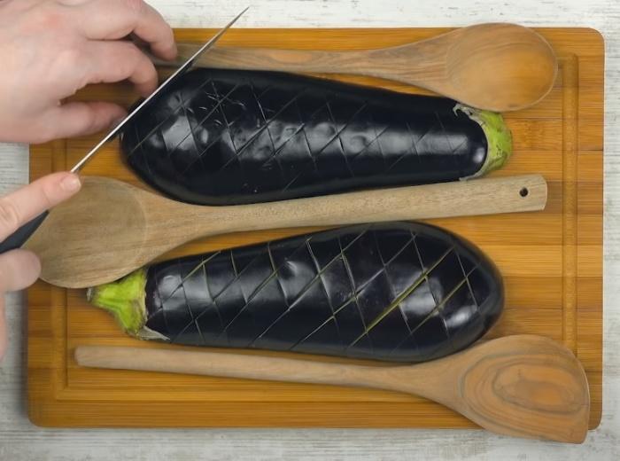 Деревянные ложки или шпажки помогают сделать глубокие надрезы, не прорезая баклажан насквозь. /Фото: youtube.com/watch?v=3JcEu9FE9us