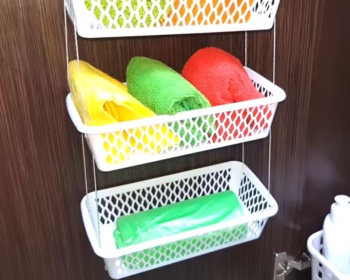 В связанных вместе корзинках удобно хранить легкие предметы на стенке шкафчика в ванной комнате.