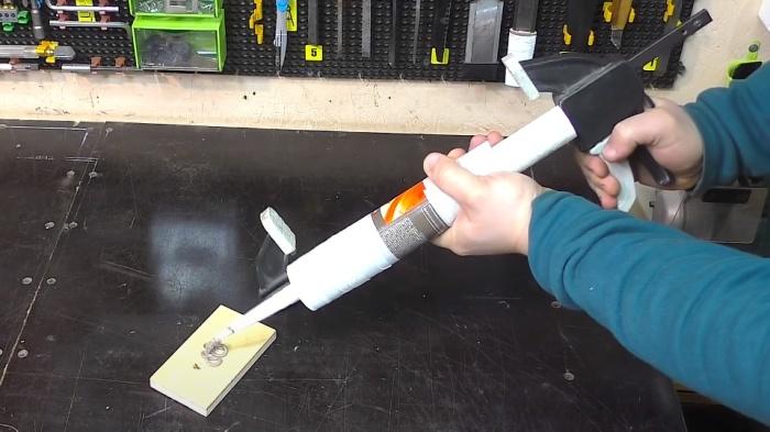 Из струбцины и куска пластиковой трубы получается неплохая замена пистолету для герметика. /Фото: youtube.com/watch?v=EqSPW0_OAPE