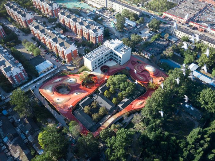 Вид сверху: детский садик плавно обтекает деревья и старинные здания. /Фото: images.adsttc.com