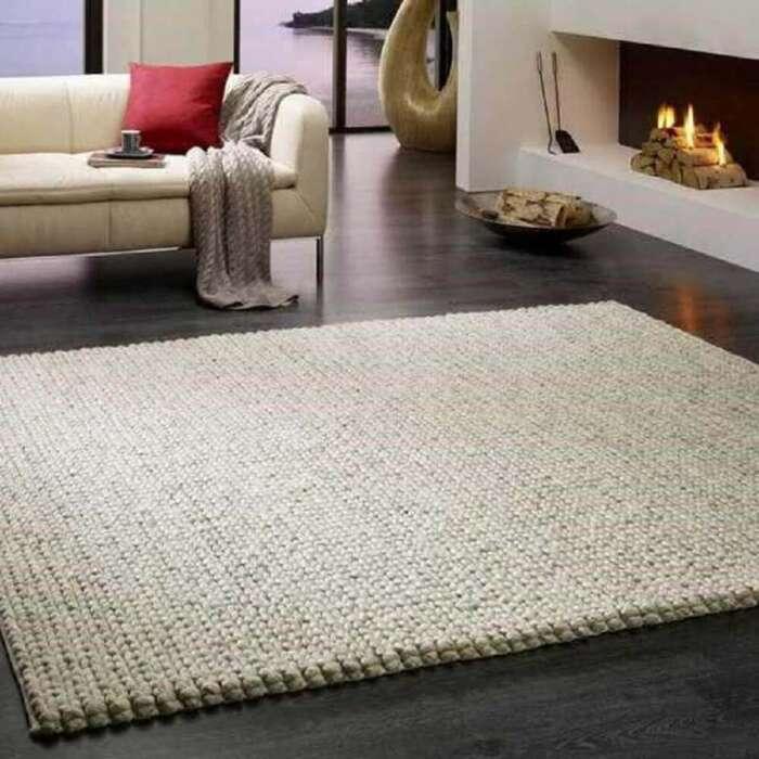 Светлый вязаный коврик хорошо смотрится в любом интерьере. /Фото: p2.trrsf.com