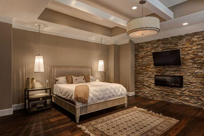 Каменная отделка стены с телевизором – популярный прием дизайна спальни. /Фото: build.4-u.info