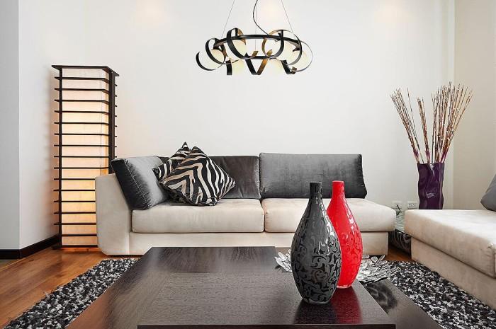 Светло-серое оформление комнаты разбавлено яркими аксессуарами и текстилем.