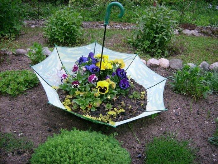 Старый зонтик будет очень эстетично смотреться в качестве клумбы с цветами. /Фото: nengen.club