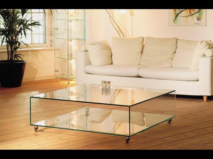 Стеклянный журнальный столик и мебель светлого оттенка визуально делают комнату светлой и просторной.