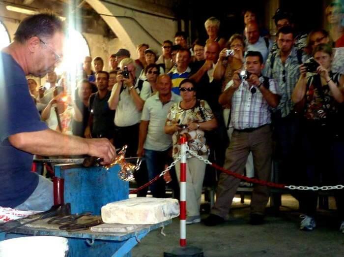 Мастер показывает туристам, как из стеклянной массы формируется фигурка. /Фото: originalmuranoglass.com