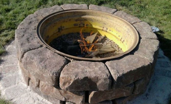 Обод колеса, обложенный кирпичом – отличное решение для костра. /Фото: hips.hearstapps.com