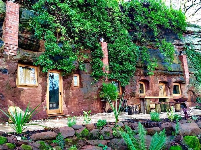 Фасад пещеры оплетен плющом, а вся территория Rockhouse Retreat окружена живописными растениями.