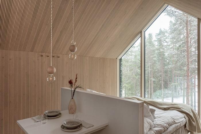 Зона столовой находится сразу за изголовьем двуспальной кровати (Niliaitta, Финляндия). | Фото: yankodesign.com.