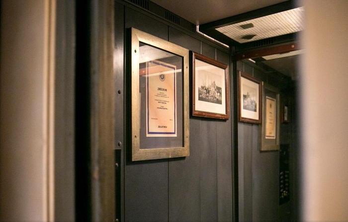 Кабина лифта украшена дипломами и любимыми фотографиями автора необыкновенной идеи.