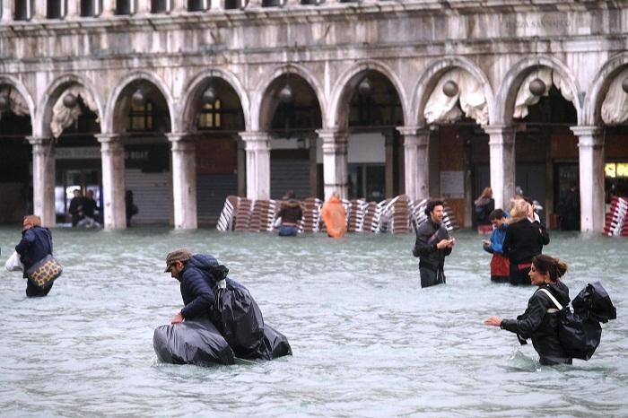 Людям по городу приходится передвигаться по пояс в воде (Венеция).