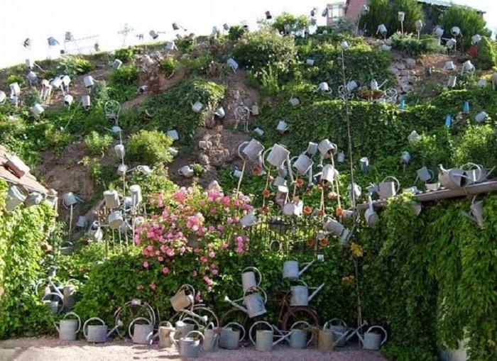 Часть коллекции леек французский флорист разместил на склоне холма («L'arroisoir», Ружмон-ле-Шато). | Фото: cpykami.ru.