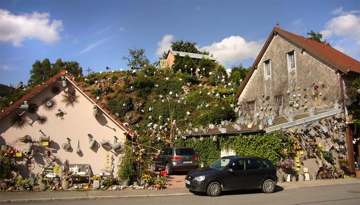 Французский флорист украсил дом, тротуар, холм и магазинчик коллекцией ...садовых леек и прославился на весь мир («L'arroisoir», Rougemont Le Chateau). | Фото: designyoutrust.com.