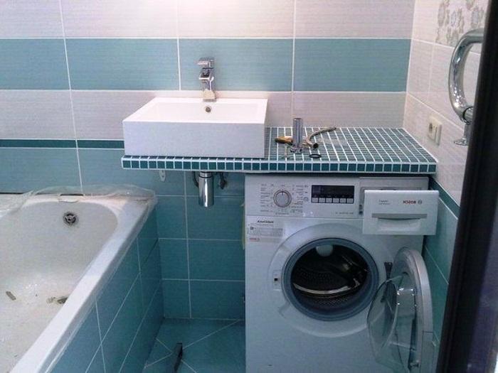 Разноуровневое размещение стиральной машинки и умывальника.
