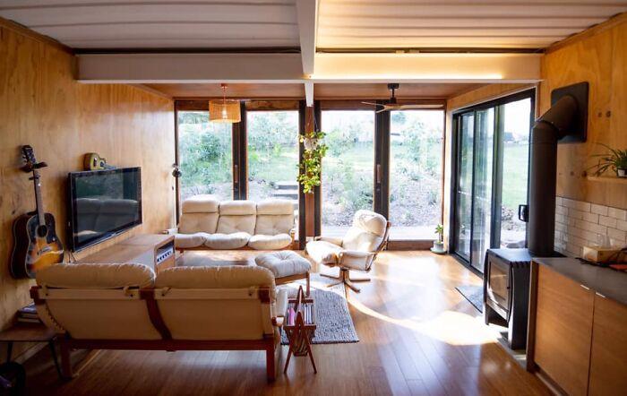 Уютная гостиная расположена у панорамного окна. | Фото: livinginacontainer.com.