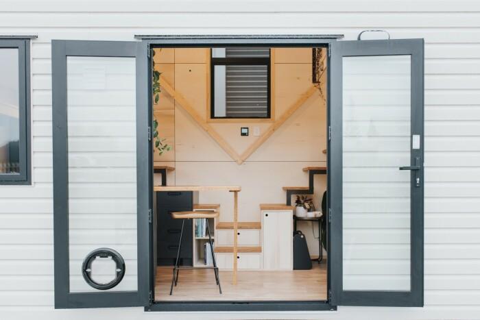 Двустворчатая стеклянная дверь с отдельным входом для кошки ведет в гостиную крошечного дома (модель The River Bank's).   Фото: autoevolution.com.