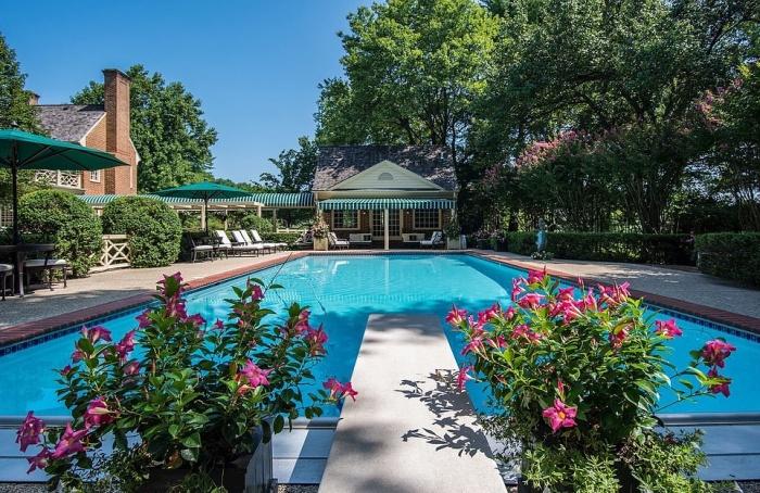 Открытый бассейн среди цветов и зелени расположен между основным домом и гостевым (Round Hill, Мэриленд). | Фото: dailymail.co.uk.
