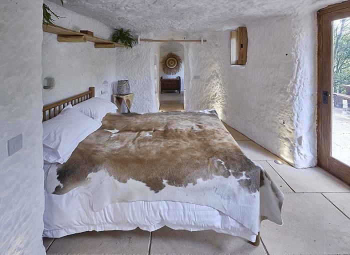 Элегантная спальня пещеры Mastropietro имеет сводчатые потолки и выход на улицу.