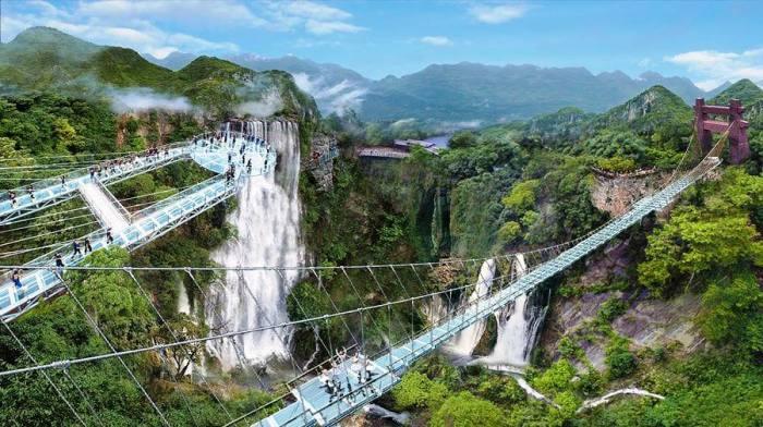 Чтобы добраться до смотровой площадки надо преодолеть не только пешеходные прозрачные мосты, но стеклянный подвесной мост (Gulongxia, Китай). | Фото: vacations.ctrip.com.