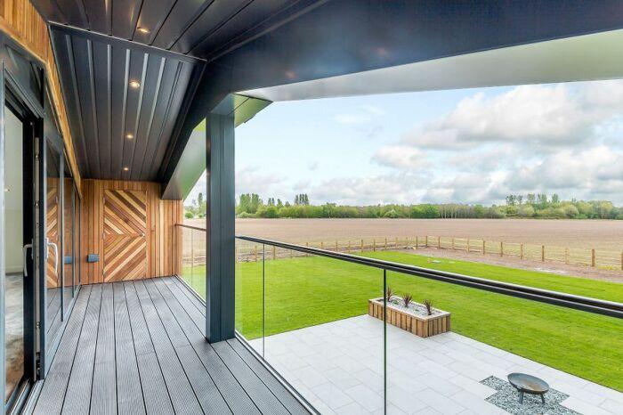 С балкона открывается фантастический вид на бескрайние поля и живописные окрестности («The Old Grain Store», Норфолк). | Фото: homes.nine.com.au.