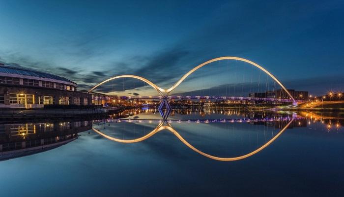 В ночное время благодаря подсветке и днем, когда полный штиль, пешеходный мост, отражаясь в воде имеет вид знака бесконечности (Мост Infinity, Англия). | Фото: liveinternet.ru.