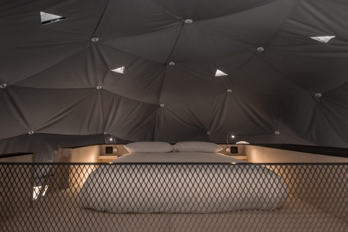 Над кроватью, расположенной на втором ярусе в полотне есть маленькие окошки, через которые можно любоваться звездным небом. | Фото: dezeen.com.