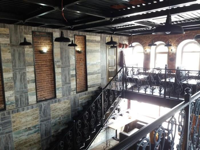 Кованная лестница, кирпичные вставки на стенах, металлические переплетения балок на потолке и удачно подобранные светильники.