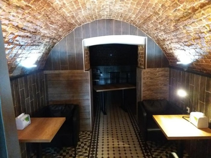 Оригинальный сводчатый потолок, деревянные столы и кожаная обивка мебели — самый оптимальный выбор в обустройстве небольших индивидуальных зон в стиле лофт.