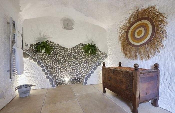 Ванная комната имеет оригинальный душ, который облицован настоящей галькой, и рукомойник, сделанный из цельного дерева.
