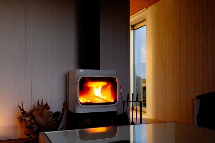 Дровяная печь с живым огнем создает особую атмосферу уюта и тепла («SynVillan», «Eriksberg»). | Фото: newatlas.com.