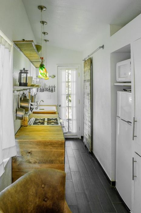 Бытовая техника, кухонные шкафы и вход в банно-прачечную зону располагается  с левой стороны домика.