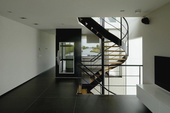 Винтовая лестница и стеклянный лифт соединяют все три уровня оригинального дома (Meerkerk, Голландия). | Фото: dezeen.com.