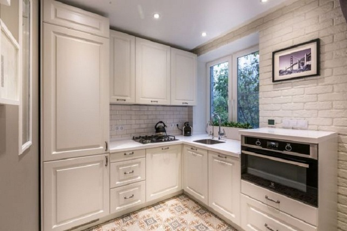 Интерьер объединенной кухни-гостиной выполнен в белых тонах