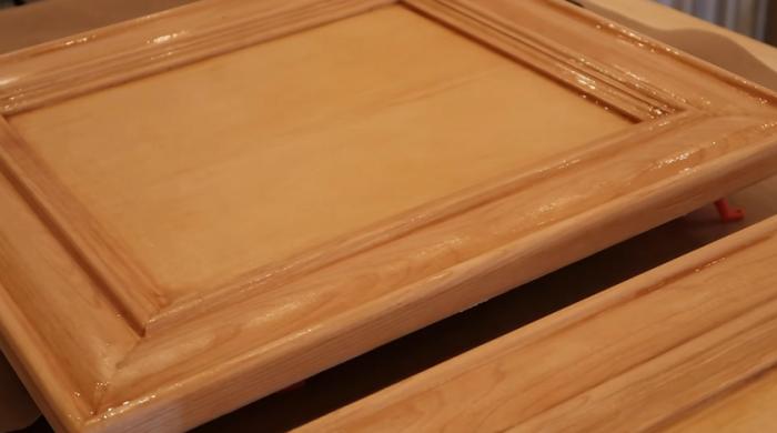 Чтобы облегчить процесс обновления дверных мебельных фасадов, их стоить снять с петель. | Фото: youtube.com/ © Living to DIY with Rachel Metz.