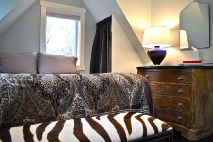 Кровать поместили на подиум и поставили дополнительный диванчик (Bird House, штат Северная Каролина). | Фото: tinyhousetalk.com.