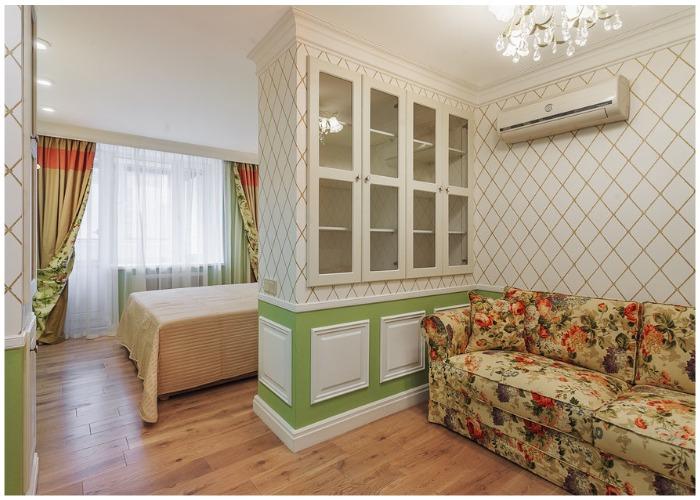 Гостиную украшают обои с классическим геометрическим рисунком и панель насыщенно зеленого цвета.