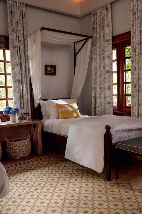 Уютная спальня, оформленная в испанском стиле с выбеленными стенами и темными деревянными окнами.   Фото: Тьяго Молинос (Tiago Molinos).