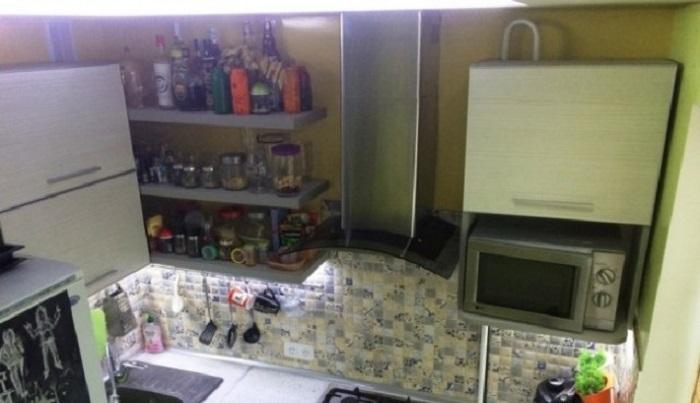 Пространство над холодильником задействовано навесными шкафами, сделанными из плит ДСП самим хозяином. | Фото: realty.tut.by.