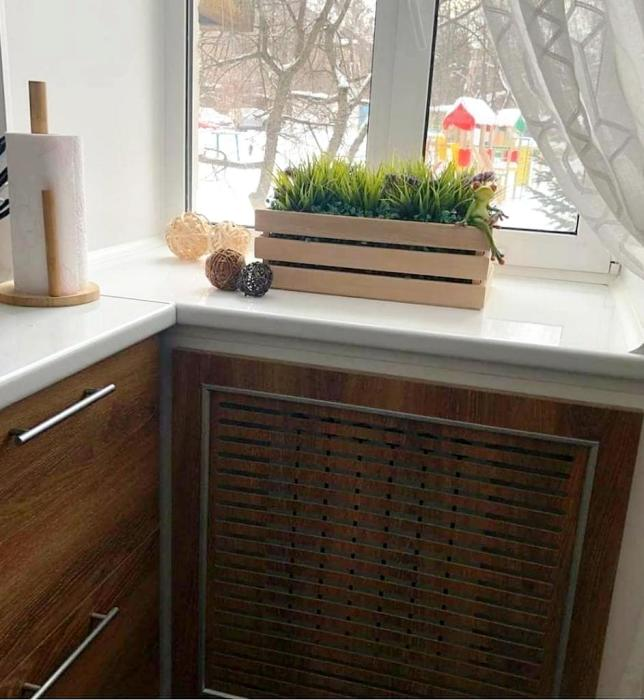 Радиатор спрятали за панелью такого же цвета, что и тумбы в рабочей зоне кухни. | Фото: lemurov.net.