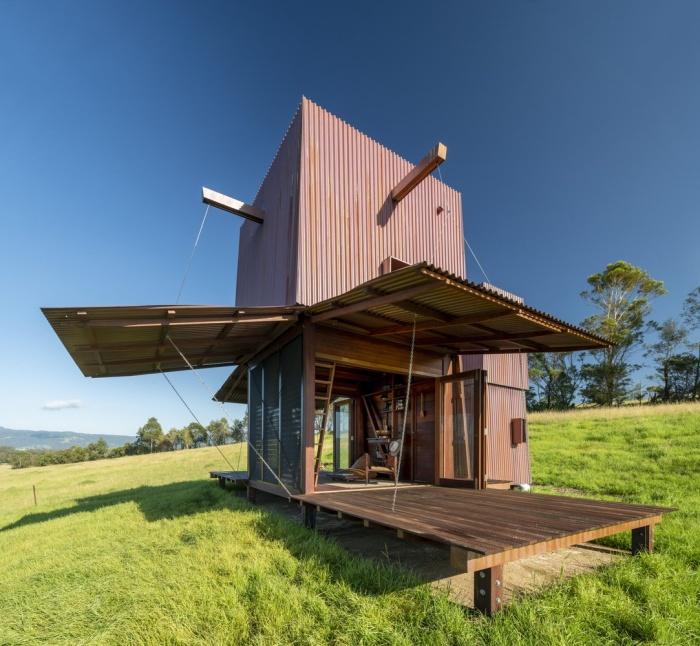 Летний дом установлен на массивной деревянной платформе, которая превращается в крытые террасы, когда поднимаются три стороны медной обшивки (Permanent Camping-2, Австралия). | Фото: builtworks.com.au.