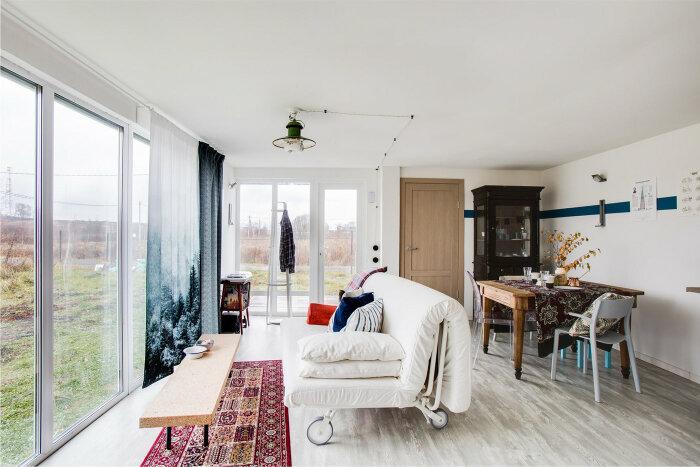 Диван в гостиной расположен напротив панорамного окна, из которого открывается прекрасный вид на природу («Небанальный дачный домик», Истра). | Фото: behance.net.