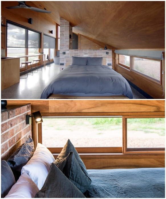 За гостиной расположена зона для сна с большой кроватью у окна (Gawthornes Hut, Австралия).