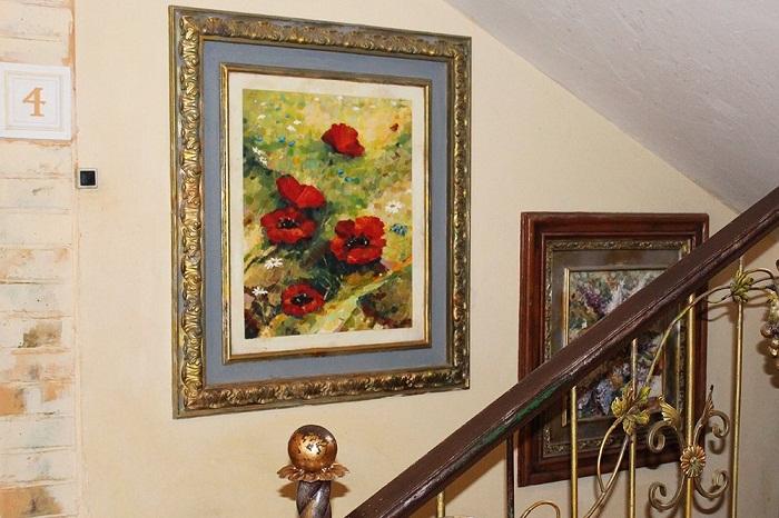 Стены лестничных полетов оформлены картинами самого автора.