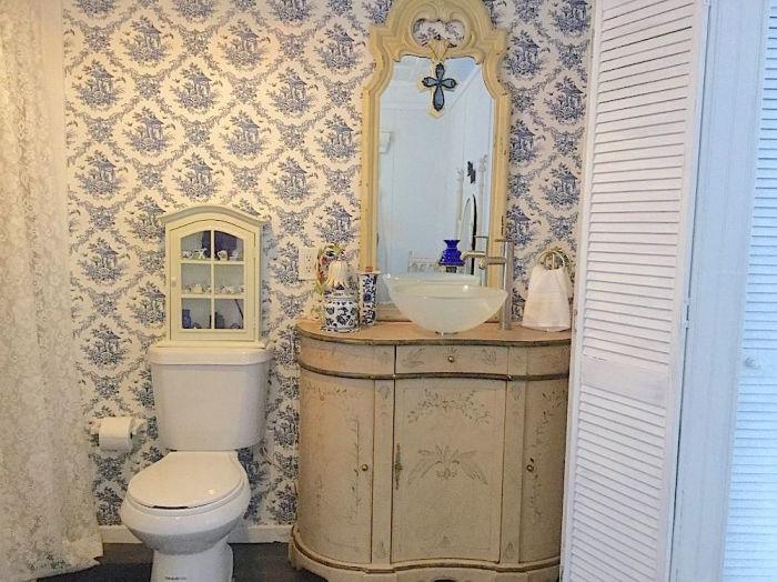 Старинный туалетный столик приспособили под рукомойник, а деревянной перегородкой отделили ванную с санузлом от жилой зоны. | Фото: fanpage.gr.