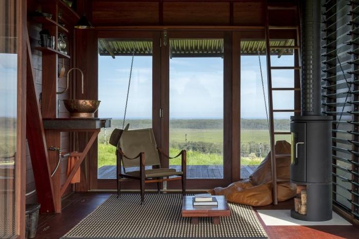 Открытая планировка нижнего уровня позволила обустроить уютную гостиную с камином (Permanent Camping-2, Австралия). | Фото: newatlas.com.