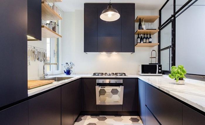 Темные матовые фасады шкафов и светлый мрамор столешниц придадут благородства даже маленькой кухне.